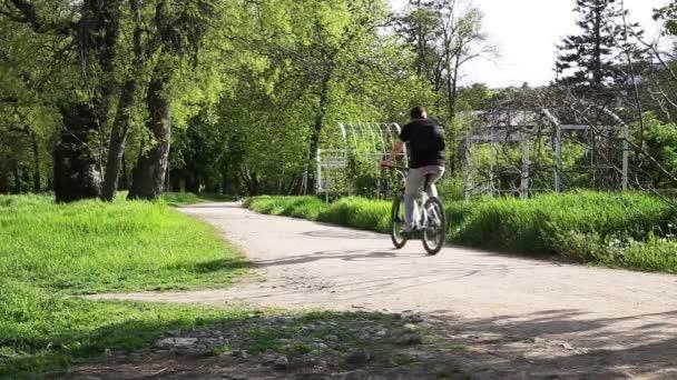 Mladý cyklista jede přes park na bílém cross-country kolo