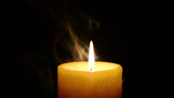 Yellow burning candle with flame and smoke