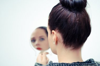 business woman looking in the mirror and reflecting on herself