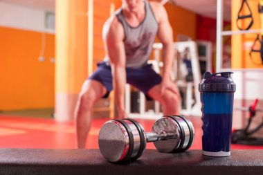 Whey protein shaker and dumbbells. Fitness and bodybuilding man