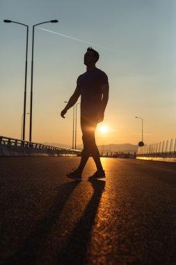 Attractive fit man running fast along big modern bridge at sunse