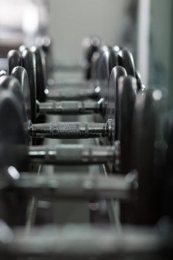 row of dumbells with lens flare and depth of field effect
