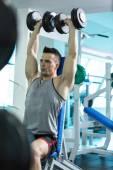 Svalnatý mladý muž dělá těžké váze cvičení pro Biceps s D