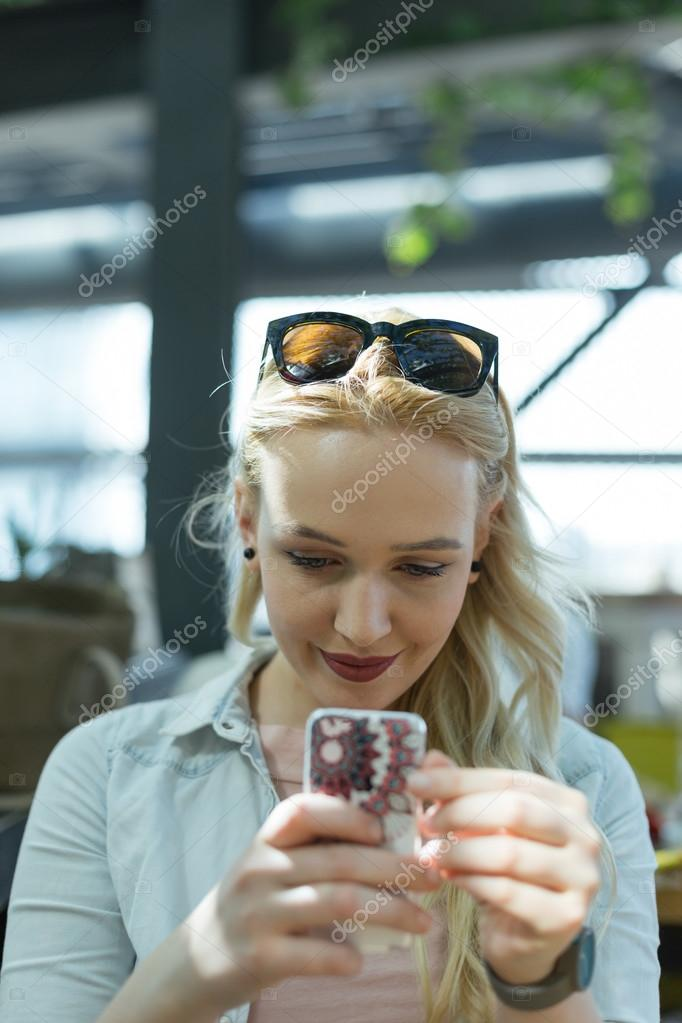 Young beautiful woman sitting at cafe and taking selfie
