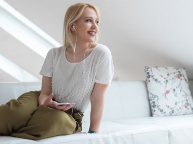 Smiling blond  woman on couch listening to music at home in the