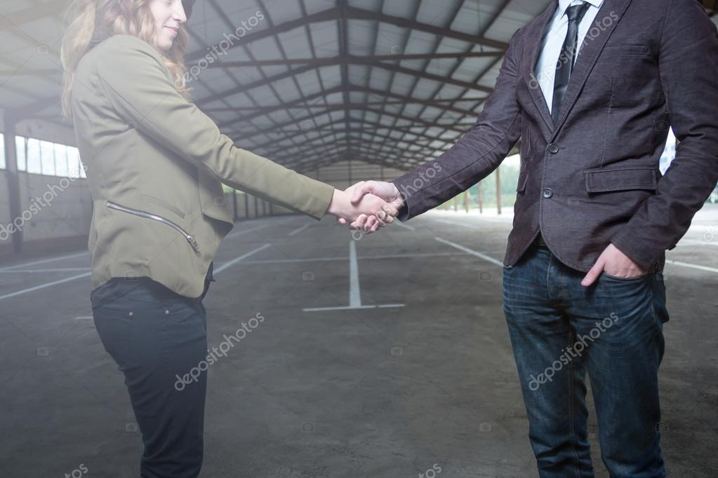 female worker shaking hands with male colleague in factory