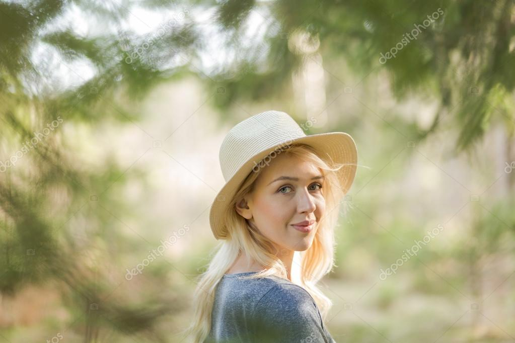 Woman in straw hat in the forest