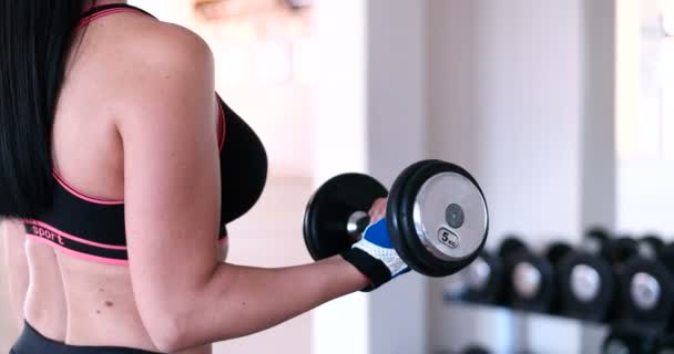 Woman in training gym with dumbbell