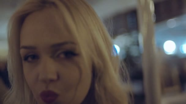 Blonde girl with red lipstick dancing and fooling around