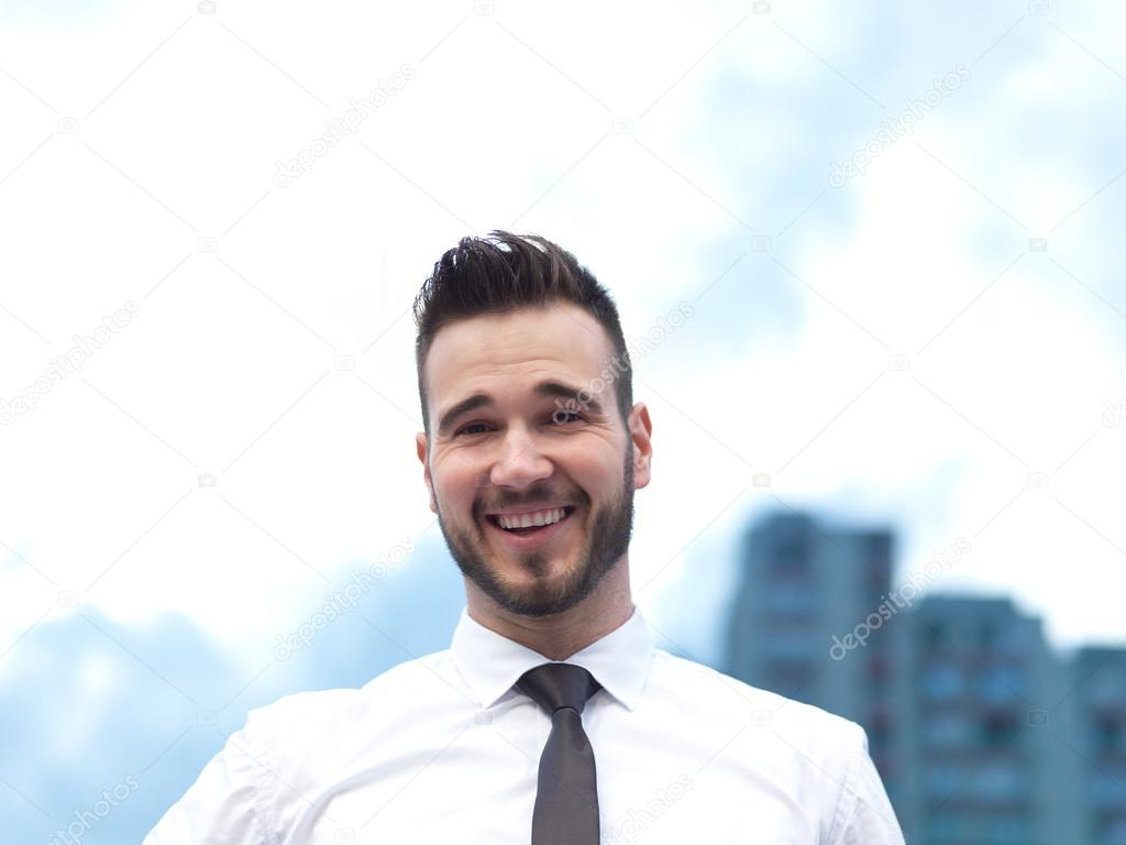 Friendly and smiling handsome businessman looking confidently at