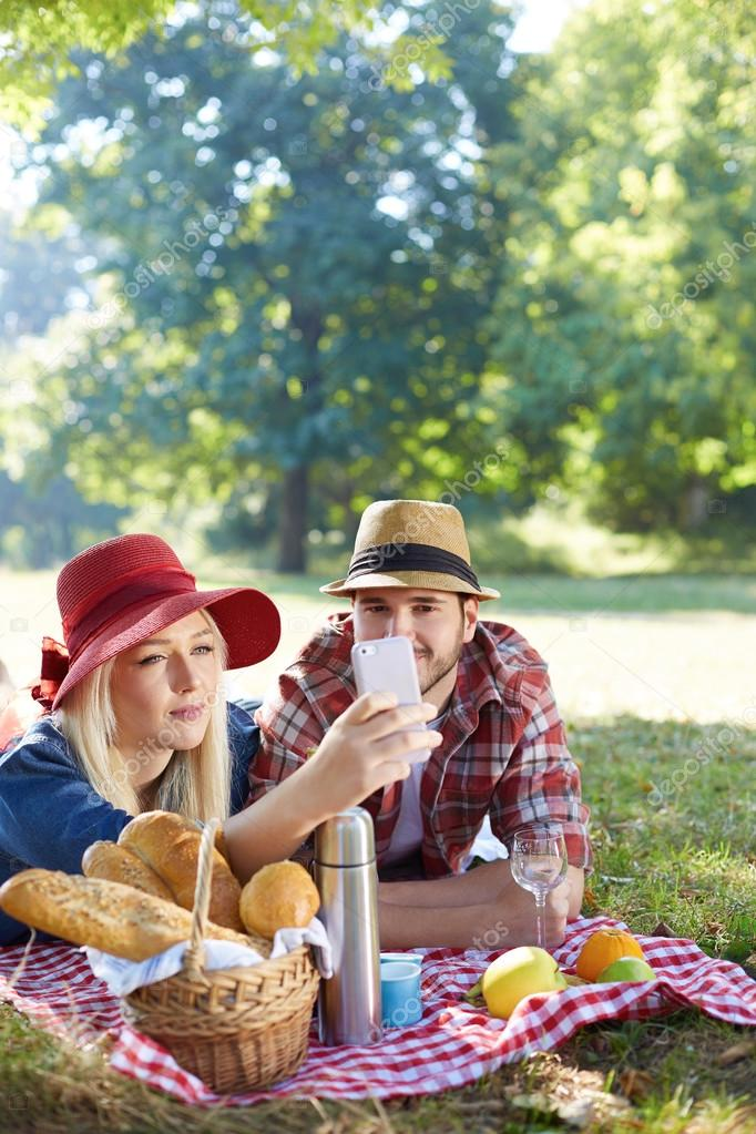 Composite of Couple taking selfie on smartphone on romantic picnic