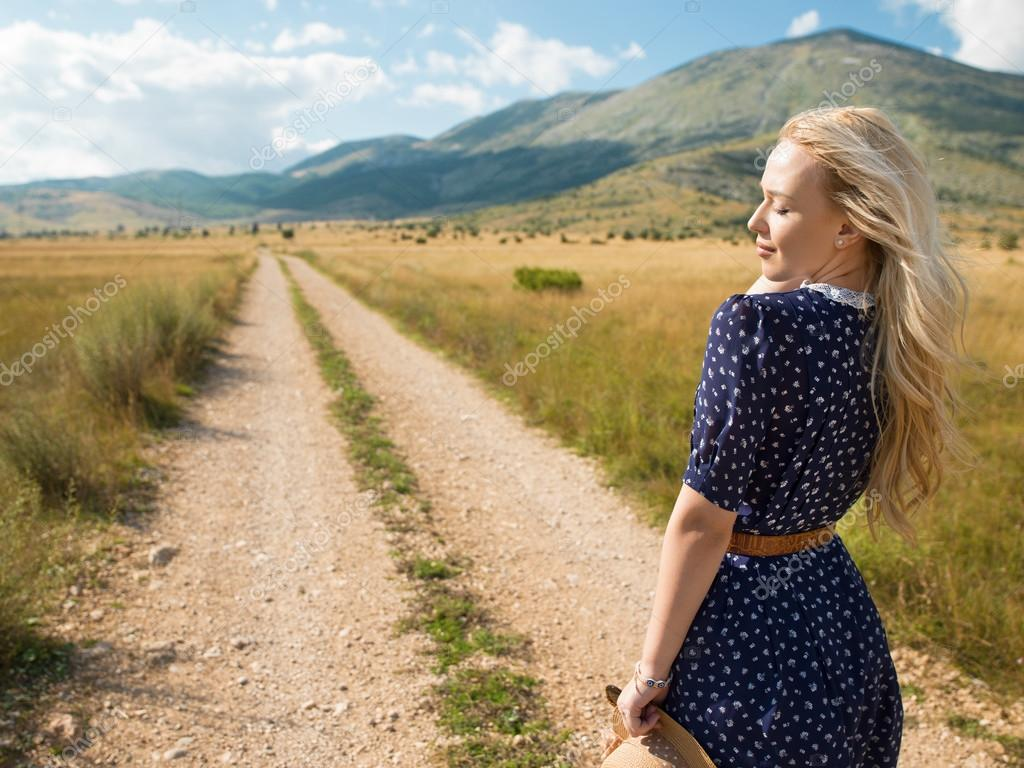 Beautiful young woman posing on a road in mountains