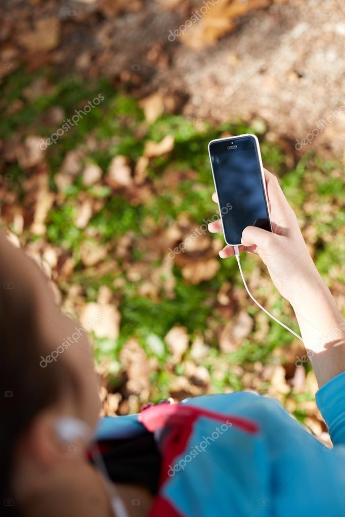 Young Sporty Woman Taking a Selfie at Park. She is Looking at Sm