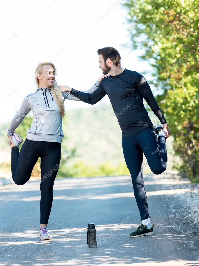 Portrait of cheerful Caucasian couple running outdoors. Runners