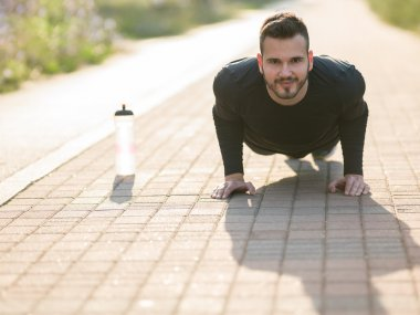 Young happuy man doing pushups exercise at morning during autumn