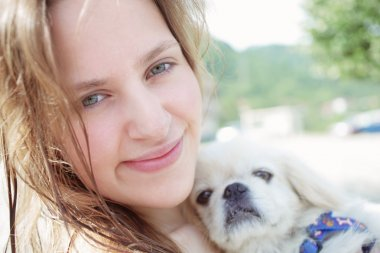 Young woman in happines emotions huging puppy