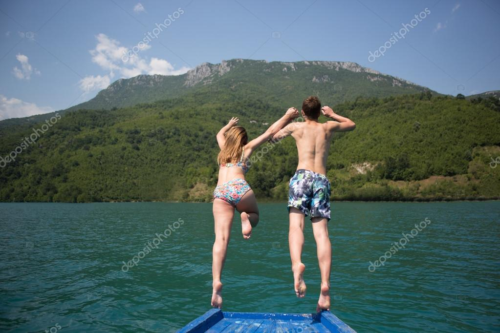 Young couple jumping on the edge of a boat