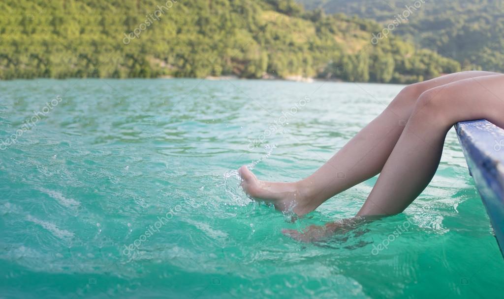 Girl's beauty legs in the lake making splashes