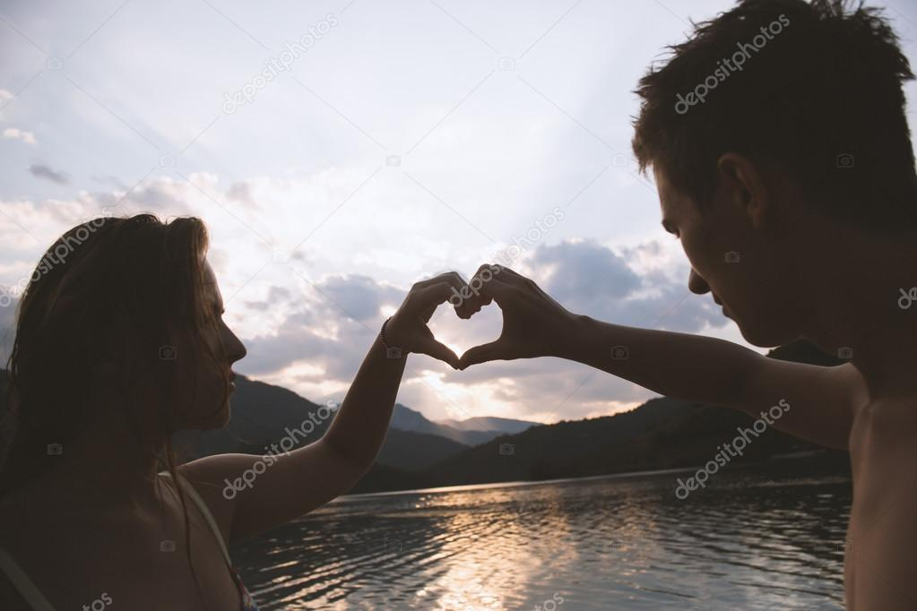 young couple making heart shape with arms on beach against golde