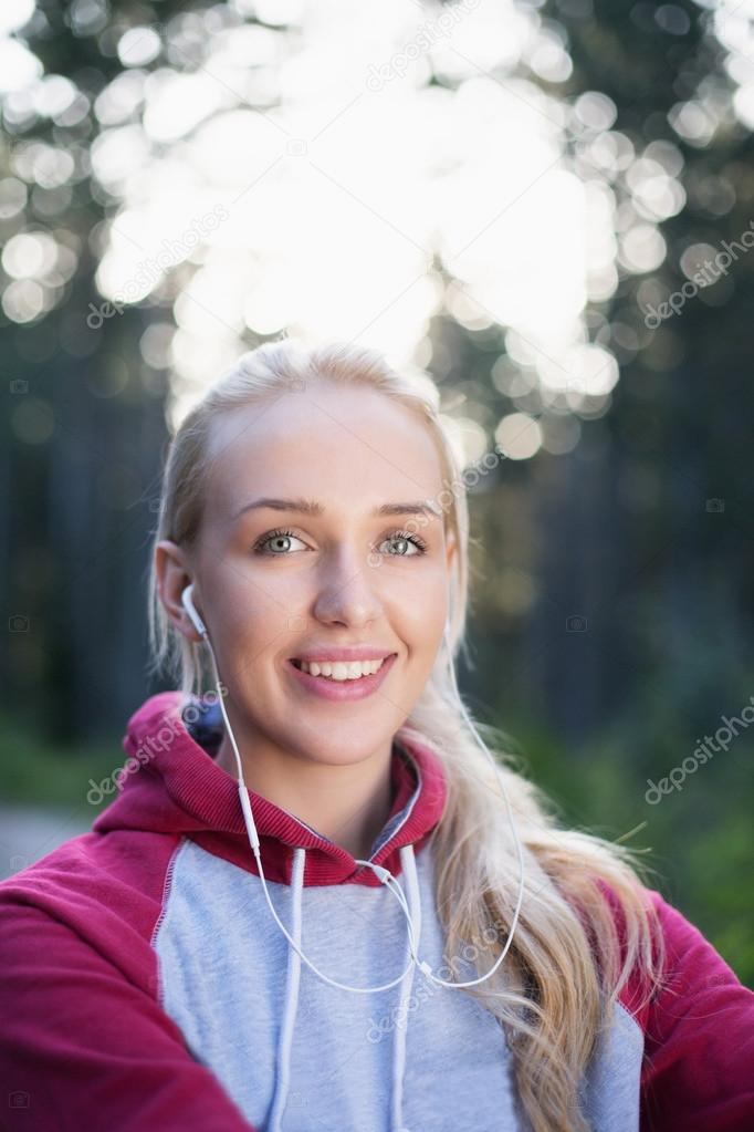 Running girl with earphones - woman runner listening to music in