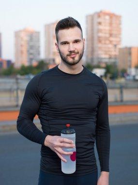 Man drinking water in urban park