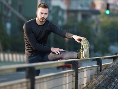 Runner stretching in urban park