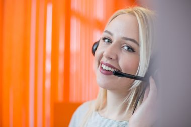 Smiling young business woman wearing a headset answering calls a