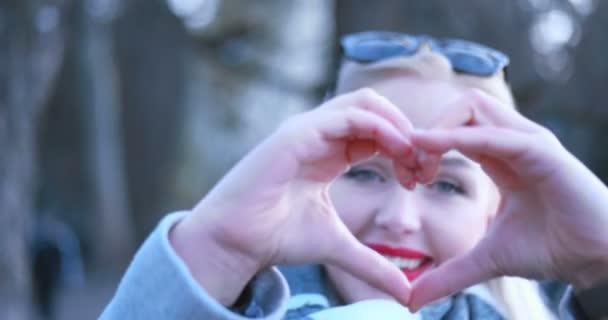 Kavkazská krásná světlovlasá žena zobrazeno srdce podepsat s prsty, valentine den pojetí lásky