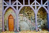 Friedberg in der Wetterau, Hessen; gotische Tür und violettes Holz an einer Steinwand. Raum für Text. Detail aus der Burg.