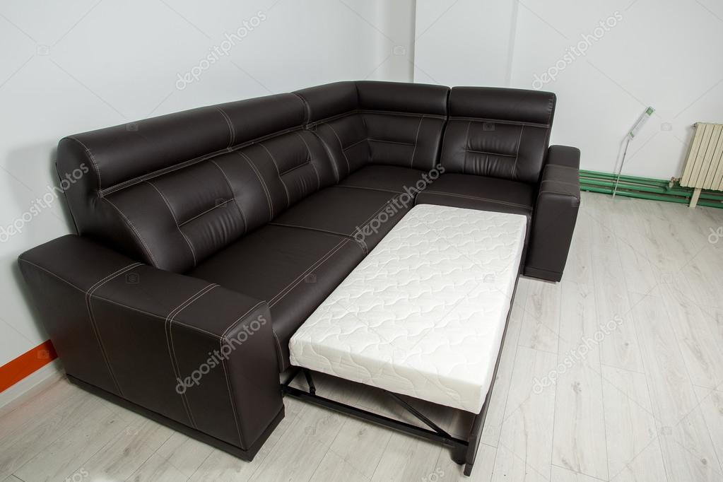черный кожаный угловой диван на нейтральный фон разлагается