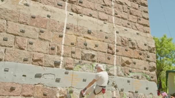 Kryvyi Rih, Ukraine - 23.05.2021 ein Bergsteiger erklimmt einen Steinstand, eine Säule einer alten Brücke, ein alter Bergsteiger Hockey ProRes 422, bmpcc4k