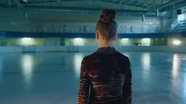a young girl, figure skater, stands on the rink, looks at the camera, the girl learns to go in for figure skating. Prores422