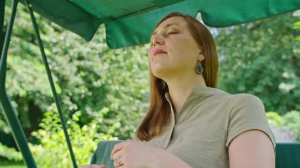 reklamní záběry, mladá dívka v létě na zahradě čte knihu, sedí na houpačce.