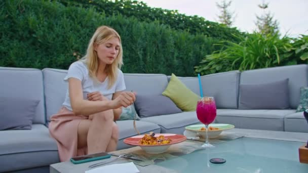 mladá žena se těší jíst těstoviny s lososem a lilkem, jíst to vidličkou v krásném chladném místě v horkém létě.
