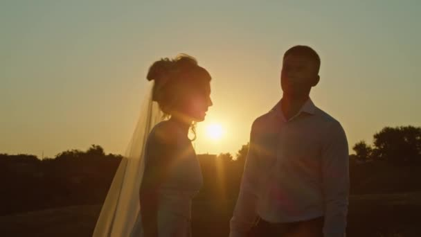 The wedding couple is having fun at sunset on the mountain hills by the river.