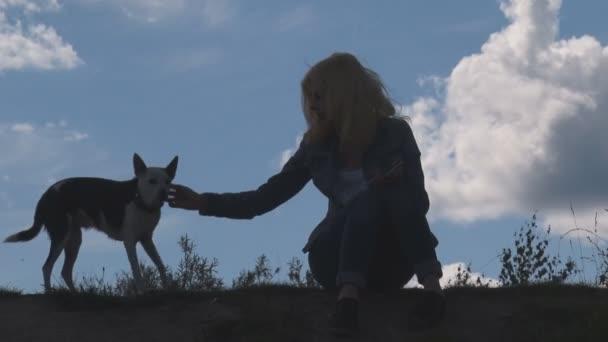 Dívka a pes na pozadí oblohy