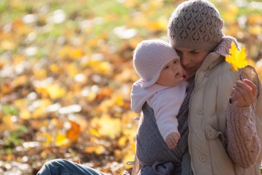 Mom and baby looking at the yellow maple leaf on outdoors