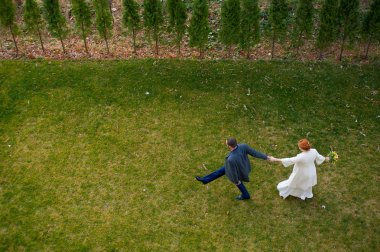 Bride and groom walking on the green grass holding hands