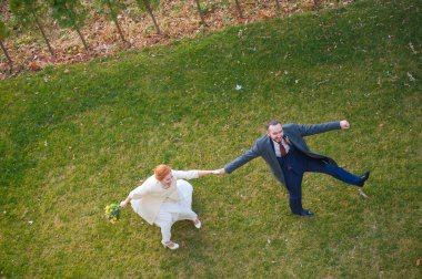 Bride and groom walking on the green grass holding hands and laughing