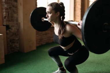 Strong woman lifting barbell