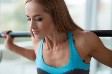 Sporty woman lifting bar