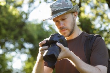 Male tourist looking captured photos at his DSLR camera outdoors