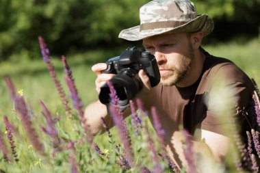Photographer shooting flowers with DSLR camera in forest