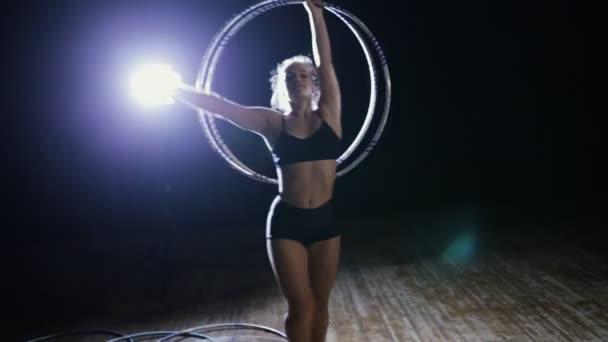 professionelle Zirkusakrobatin dreht Hula-Hoop-Reifen auf der Bühne