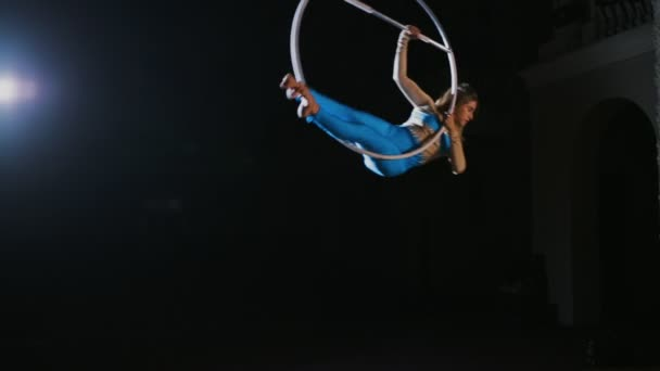 Circus performer hanging on aerial hoop and doing some acrobatic elements