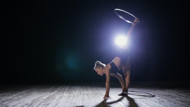 Akrobatikus nő előadóművész forgatni hula hoop sötét jelenet