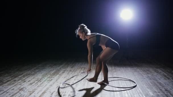 Akrobatische Darstellerin dreht Hula-Hoop-Reifen in dunkler Szene