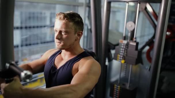 Muž čerpání své svaly na aparát tréninku v tělocvičně