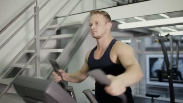 Mužské sportovce dělat kardio cvičení na přístroji trénink v tělocvičně