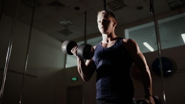 Atletický muž čerpání biceps s činka v posilovně